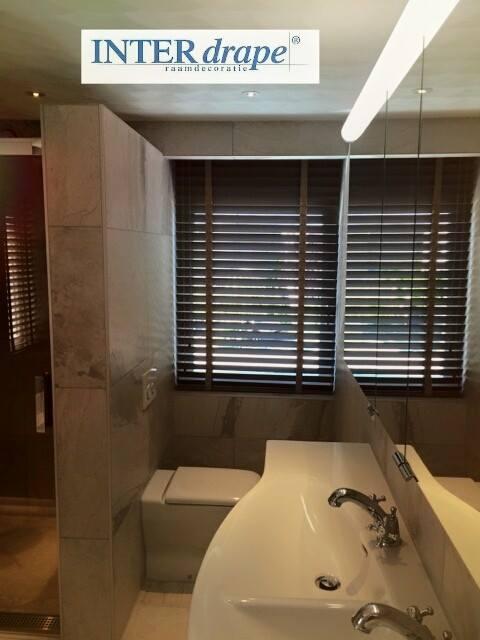 Badkamer voorzien van een houten jaloezie.